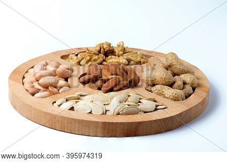 Mix Of Raw Dried Nuts On Wooden Plate Isolated On White.