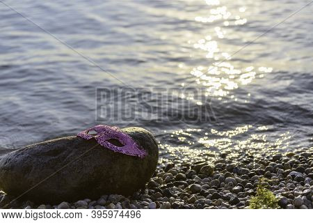 Pink Glitter Mask Forgotten On A Stone By The Lake. Rays Of Light On The Water And On The Stones Of