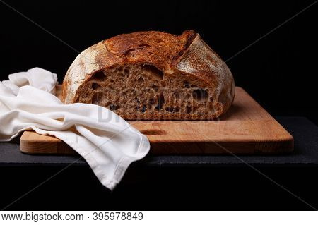 Artisan Sourdough Bread. Freshly Baked Round Loaf Of Sourdough Bread With Linen Cloth On Black Backg