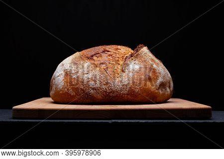 Artisan Sourdough Bread. Freshly Baked Round Loaf Of Sourdough Bread On Black Background.