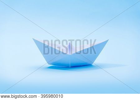 White Paper Boat On A Blue Background, A Boat Floating On The Water, A Symbol Of Hope, Origami, Clas