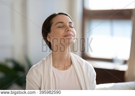 Content Woman Sitting On Sofa With Closed Eyes Breathing Air