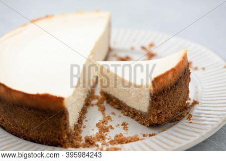 Plain New York Cheesecake With Slice Cut Out On A Plate, Closeup View. Tasty Cheesecake