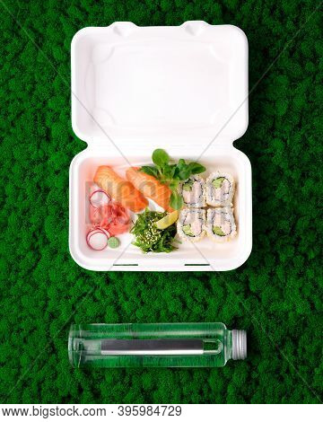 Sushi Set In Takeout Box With Water In Glass Bottle On Green Moss Background. Salmon Sashimi, Califo