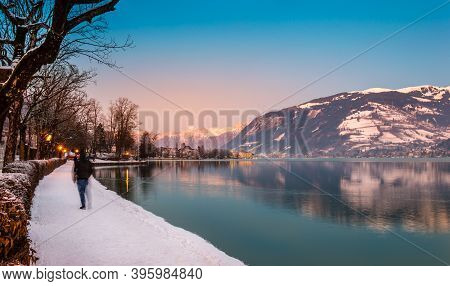 Zell Am See In Winter Evening. Esplanade Along Lake Zell, Blurred Tourist, Town, Mountains And Snow