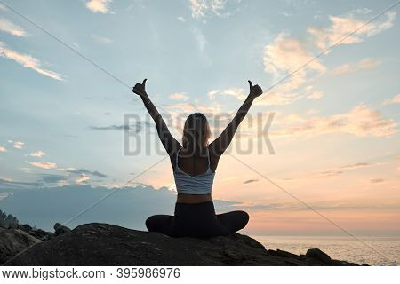 Woman Practicing Yoga In The Nature. Thumbs-up. Meditating Outdoors