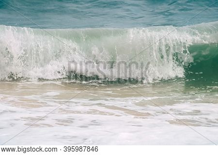 Turquoise Waves With White Foam On The Banks Of Benagil Beach In Portugal