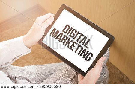 Man Using Digital Tablet, Close-up, Coffee And Keyboard On The Background. Text Digital Marketing