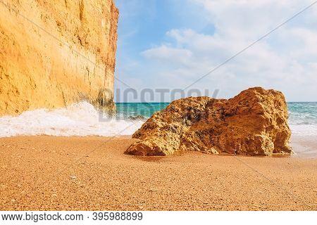 Waves Crash On Rocks On The Sandy Shores Of Benagil Beach In Portugal
