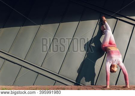 Athetic Girl Doing Handstand Against The Wall On The Street