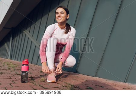Athletic Girl While Running Squatted To Tie Shoelaces