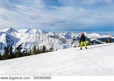 Snowboarder On Slope Against Mountains And Sunset In Winter Ski Resort Zell Am See In The Alps, Aust
