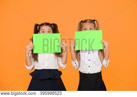 Wow. Little Girls Holding Empty Sheets Of Paper On Yellow Background. Small Children With Blank Gree