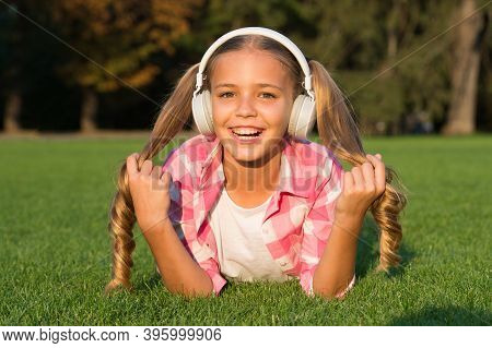 Learn Any Language In Fun Way. Happy Kid Wear Headphones Lying On Green Grass. Foreign Language Cour