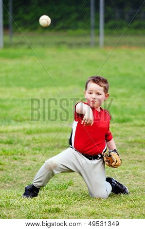 Child in uniform throwing baseball during game
