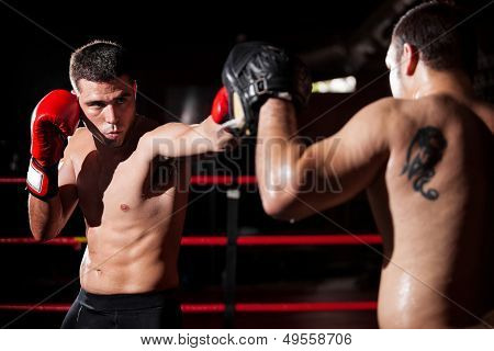 Boxer and coach training in a ring