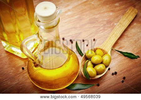 Olive oil with fresh olives on rustic wood