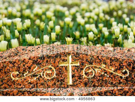 Cross On Gravestone With Flowers