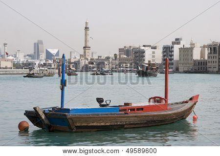 Dubai UAE empty abra anchored on Dubai Creek with minaret of Grand Mosque in distance