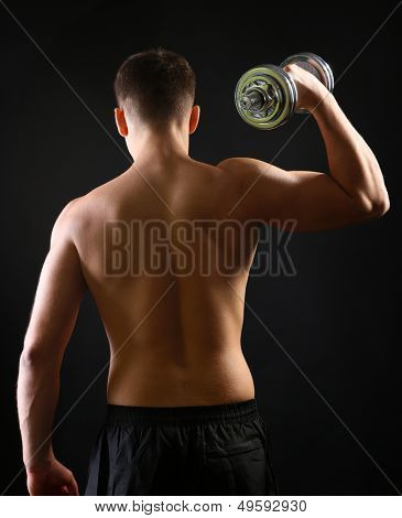Handsome young muscular sportsman execute exercise with dumbbell on dark background