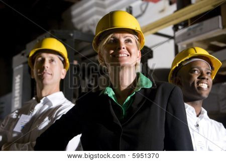Office workers in storage warehouse wearing hard hats