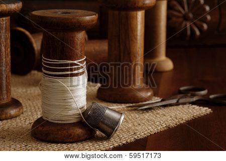 Sewing still life with antique thimble, scissors and wooden spools (from old textile mill - circa 1900). Antique sewing machine drawer in background. Macro with shallow dof.