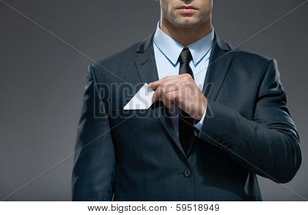 Part of body of man who pulls out white card from the pocket of business suit, copyspace
