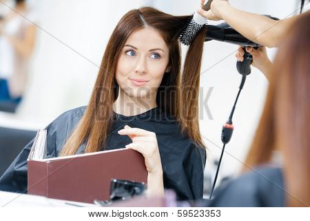 Reflection of hairdresser doing hair style for woman in hairdresser's. Concept of fashion and beauty