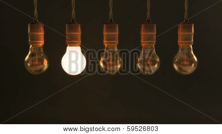 Five Hanging Vintage Incandescent Light Bulbs With One Illuminated