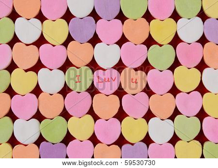 The words I Luv U spelled out on candy hearts.  The hearts are arranged in straight rows with the three middle candies having words only. Great for Valentine's Day projects.