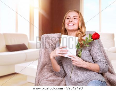Happy female enjoying greeting card, reading with pleasure love letter, receive red rose, celebrate Valentine day at home