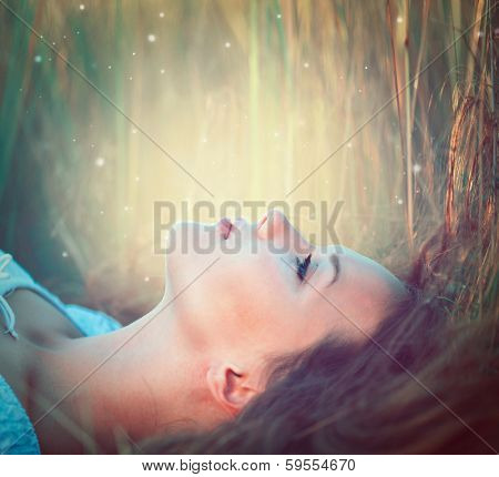 Beauty Romantic Girl lying on the Field and dreaming. Beautiful Teenage Model girl outdoors enjoying nature. Fantasy scene. Magic Backlit. Warm colors