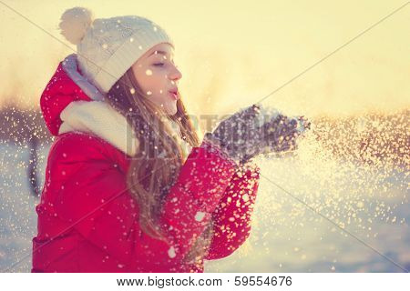 Beauty Winter Girl Blowing Snow in frosty winter Park. Outdoors. Flying Snowflakes. Sunny day. Backlit. Joyful Beauty young woman Having Fun in Winter Park. poster