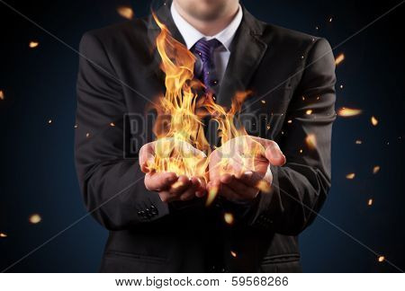 Businessman with fire in hands. Concept of threats and manager responsibility poster