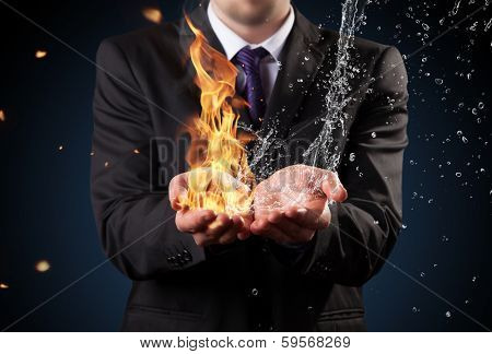 Businessman with fire and water in hands. Concept of threats and solutions as so as manager responsibility and power poster