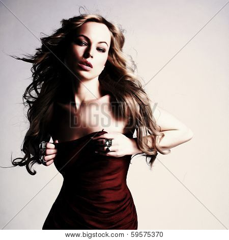 portrait of sexy caucasian young woman in red dress with long blond hair, beautiful eyes, sensual lips and clean skin