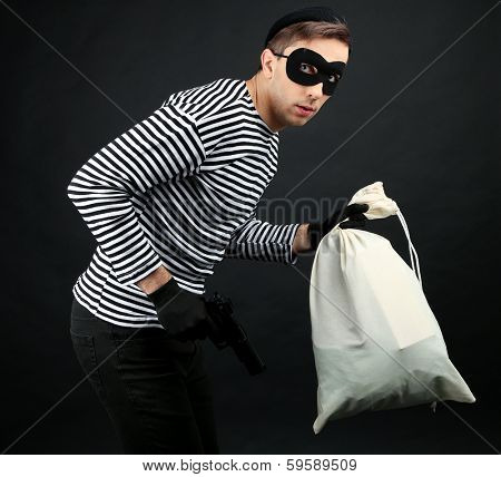 Thief with bag isolated on black