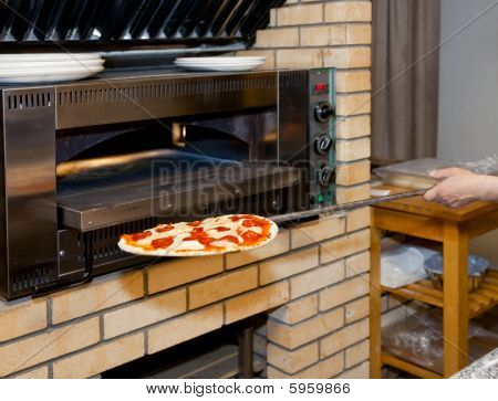 Man Inserting Pizza In Oven