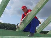 Roofer posing on house rafter beam against the sky poster
