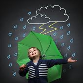 Young happy child singing and dancing holding an umbrella standing in front of a chalk drawing of a rain and lightning storm on a school blackboard poster