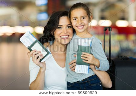 beautiful mother and daughter holding passports and boarding pass at airport