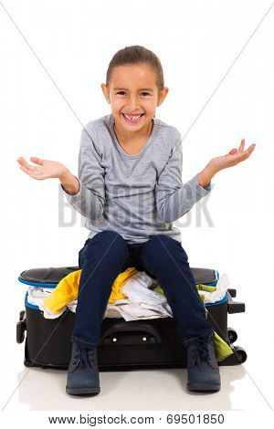 cute little girl sitting on overfilled suitcase