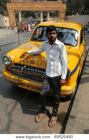 KOLKATA, INDIA - FEBRUARY 14: Indian taxi driver posing in front of his cab in Kolkata on February 14, 2014. The car is Hindustan Ambassador, manufactured since 1958.