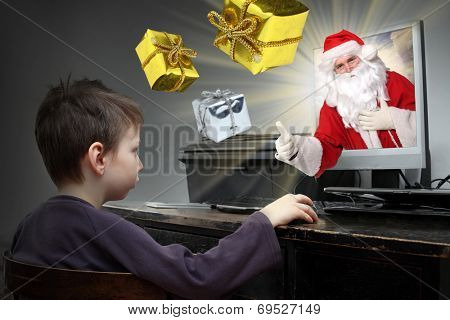 Happy boy buying christmas gifts in eshop with Santa Claus.