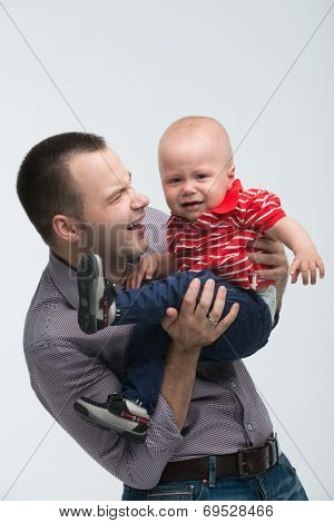 Cute toddler boy is naughty on dads hands