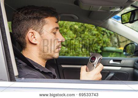 Man Looking At Breathalyzer