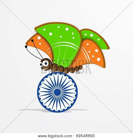 Butterfly with shiny saffron and green color wings sitting on Asoka Wheel on grey background for 15th of August, Indian Independence Day celebrations.