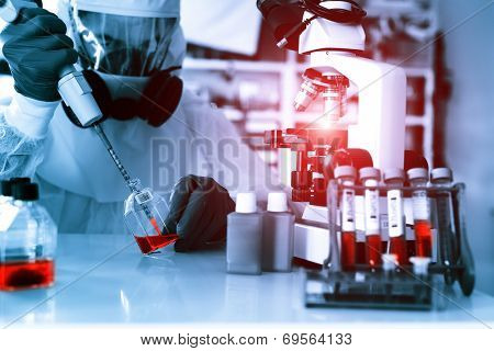 Laboratory examination of Ebola. Scientist takes blood pipette and microscope studies in biological samples.