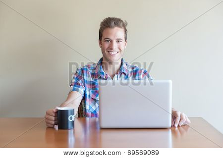 Young Adult Using Computer And Holding Cup Of Coffee