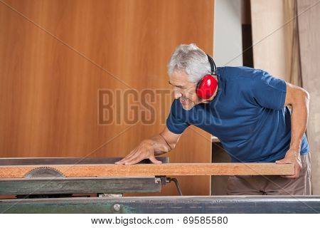Senior male carpenter cutting wooden plank with tablesaw in workshop
